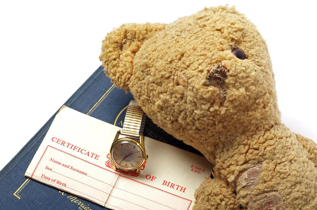 birth certificate alongwith wrist watch and a teddy bear